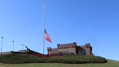 Long Distance Shot of Hillside Military-like Structure with Flag at Half Mast Stock Footage