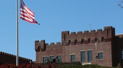 Castle-like Building Behind US Flag Waving at Half Mast Stock Footage