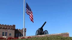 Canon in Foreground of US Flag at Half Mast with Building in Background Stock Footage