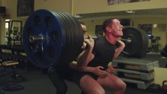 Sportsman perform exercises a squats with a barbell in the gym with the trainer Arkistovideo