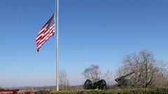 US Flag at Half Mast Waving over Hilltop Lined with Canons Stock Footage