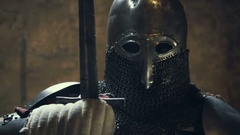 Medieval knight with sword and shield against stone wall Stock Footage