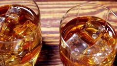 Glasses of malt whiskey on a wooden table Stock Footage