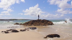 Man Standing on Rocks on the Shore Stock Footage