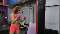 Fitness woman hitting the punching bag and practicing kick boxing Stock Footage