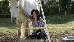Young rider brunette girl with her white horse, slow motion Stock Footage
