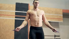 Fit young man doing jump rope exercises at gym Stock Footage