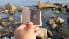 Time to travel, hand holding a book with the inscription and rocks on the sea Stock Footage