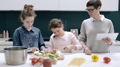 Mom teaching kids to cook a meal with a digital tablet Stock Footage