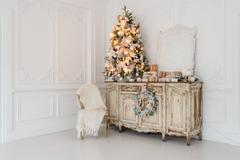 Christmas tree on wooden chest of drawers commode bureau in white interior Stock Photos