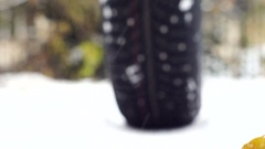Snow tire rolls away and towards the camera Stock Footage