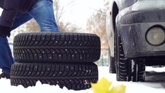Man puts a set of new snow tires near a car Stock Footage