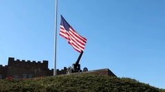 American Flag at Half Mast over Artillery Canon Stock Footage