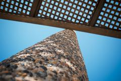 Low angle view on wooden shade of seating bench with pebble stone column Stock Photos