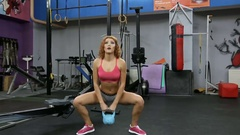 A young woman with a kettlebell squats at the gym Stock Footage