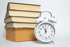 Alarm clock and books on white background Stock Photos