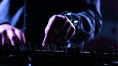 Close-up footage of a male DJs  hands mixing music at a party by using his Stock Footage