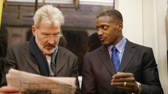 4K Two businessmen discussing a newspaper article on a train as they commute Stock Footage
