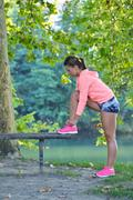 Runner girl tying laces shoes at the bench Stock Photos