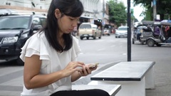 Young woman browsing on her smartphone while sitting in the city Stock Footage