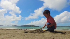 Kid at Mahurangi beach, using his spade to make sand castle. Stock Footage