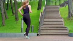 Woman running up stairs in slow motion. Real women run upstairs in park Stock Footage