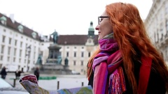Young red hair woman using city map in Vienna, wide angle, close up Stock Footage