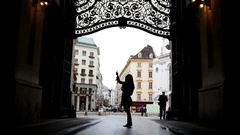 Woman using cell phone in hofburg Vienna, silhouette, wide angle Stock Footage