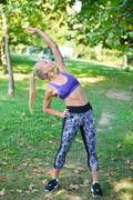 Young girl stretching outdoors. Jogging - workout preparations. Stock Photos