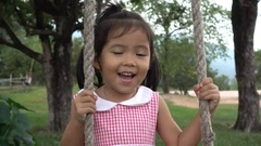 Cheerful little girl standing on wooden swing and enjoy by bubbles Stock Footage