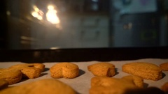 Man pulls out ginger biscuits out of the oven Stock Footage