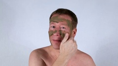 Handsome Man applies cosmetic mask. White background. Stock Footage