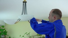 Electrician man climb up and change light bulb to economic one Stock Footage