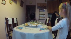 Family covers festive table in the kitchen and sits down to eat and celebrate Stock Footage