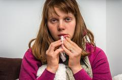 Sick woman having flu and sneezing into handkerchief at home Stock Photos