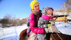 Mother and her two great sons in warm clothes are on the horse. Stock Footage