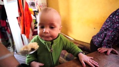 Little child is being fed. His elder brother is nearby. Stock Footage