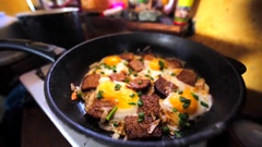 Closeup of fried eggs on a frying pan with a few slices of bred and leek. Stock Footage