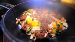 Fried eggs on a frying pan with a few slices of bred. Stock Footage