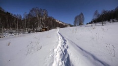 Walking slowly along the snowy path in the Chachzaevka Ecovillage Stock Footage
