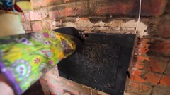 Openning the russian stove and takes a frying pan with hot homemade bread. Stock Footage