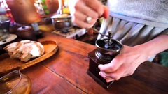 Woman is grinding coffee beans with an old coffee grinder. Stock Footage