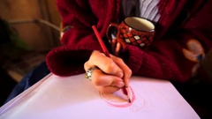 Unidentified girl drawing something with red pencil and holding a cup of coffee Stock Footage