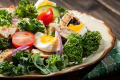 Fresh salad with chicken, tomatoes, eggs and lettuce on plate. Healthy food Stock Photos