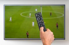 Man is watching football match on TV and holding tv remote controller in hand Stock Photos
