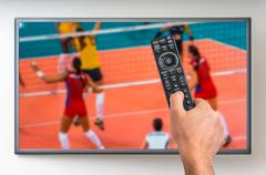 Man is watching volleyball match on TV and holding tv remote controller in ha Stock Photos