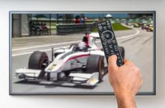Man is watching formula one racing on TV and holding tv remote controller in  Stock Photos