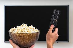 Man is going to switch on TV and holding tv remote controller and popcorn in  Stock Photos