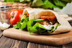 Pita bread with falafel and fresh vegetables on wooden table Stock Photos