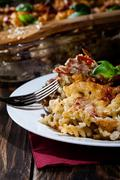 Portion of fusilli pasta casseroles, sausages and zucchini on a plate Stock Photos